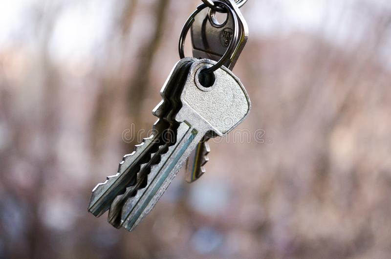 Ключи пук пользуется ключом белизна Ключи к квартире Фотография для вебсайтов о продаже квартир и домов, недвижимости стоковые изображения