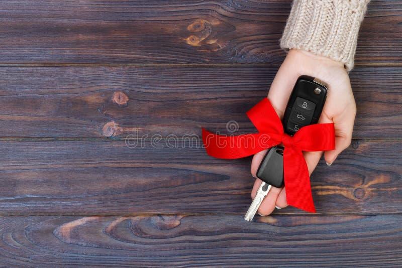 Ключ автомобиля владением руки женщины с красным смычком Давать автомобиль как подарок стоковое фото