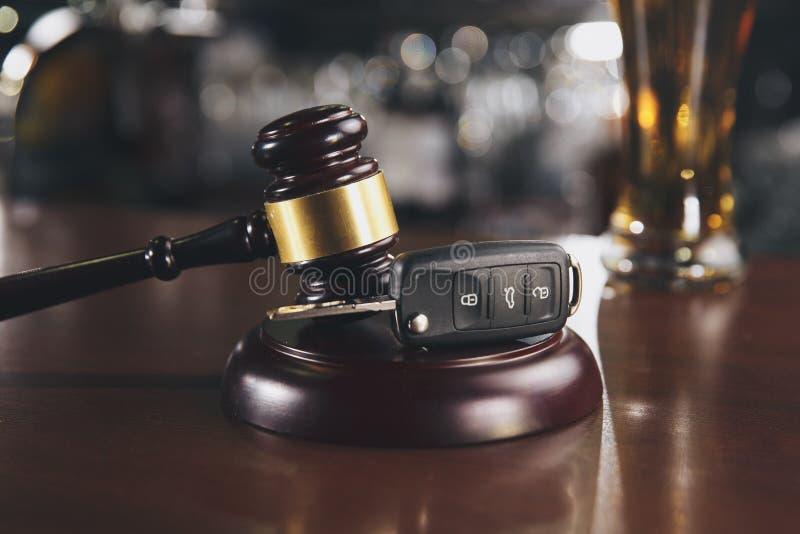 Ключ автомобиля и алкогольный напиток пива в стекле на коричневом деревянном столе Не выпейте стоковые изображения