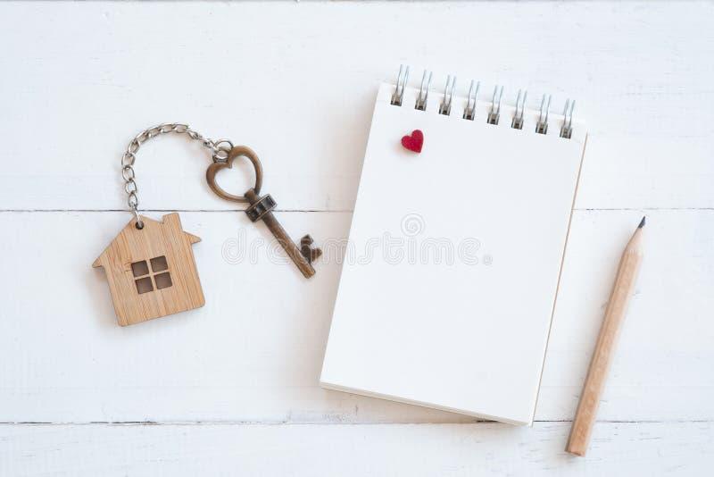 Ключ дома с домашним кольцом для ключей, пустой тетрадью и карандашем на белой деревянной предпосылке таблицы стоковое фото