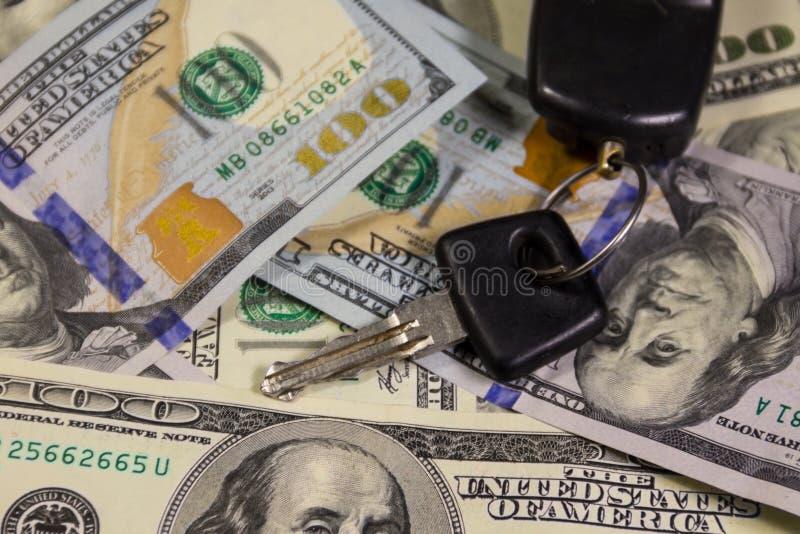 Ключ с кольцом автомобиля ключевым на предпосылке долларовых банкнот американца 100 стоковая фотография