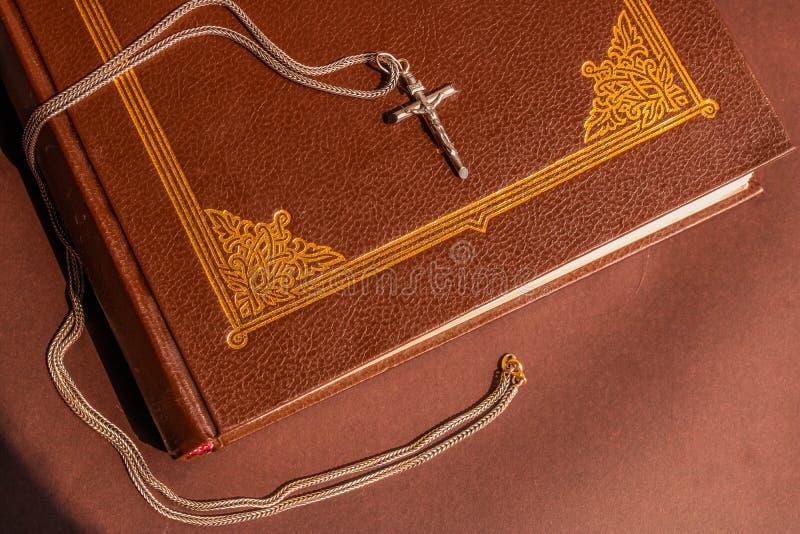 Книга библии Брауна и простой серебряный крест на ем Религиозная концепция стоковая фотография