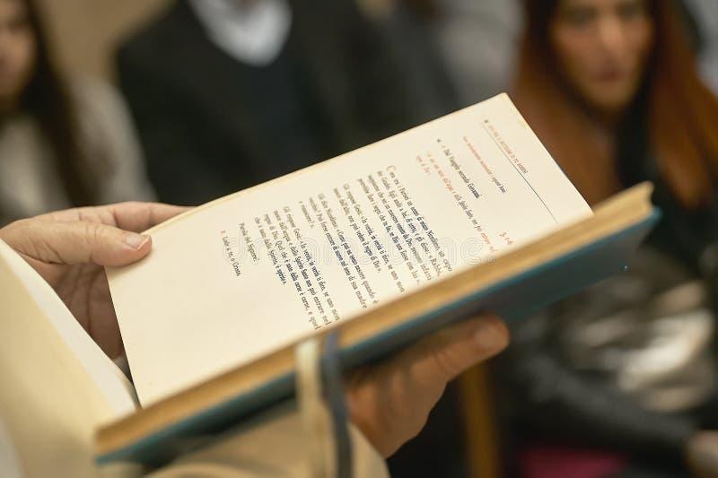 Книга Евангелия держала священником стоковая фотография