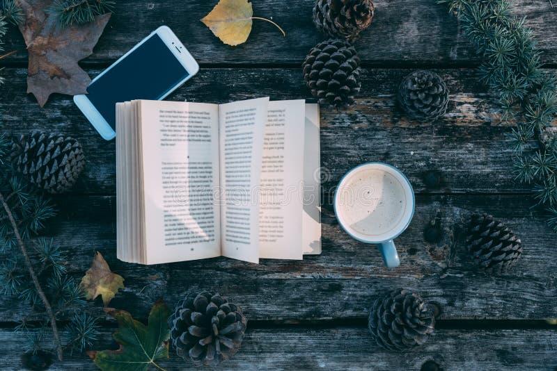 Книга и мобильный телефон на деревянном столе с кофе и ou сосен стоковая фотография rf