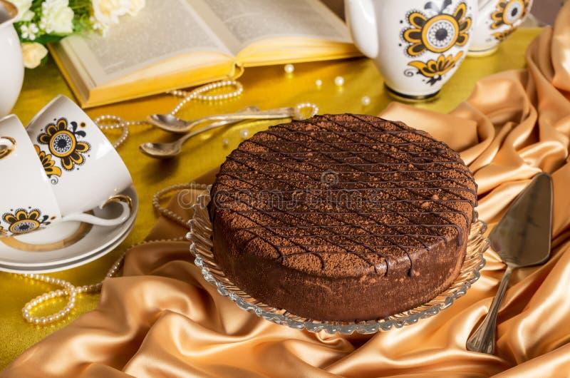 Книга и шарики комплекта чая шоколадного торта на ткани стоковые изображения