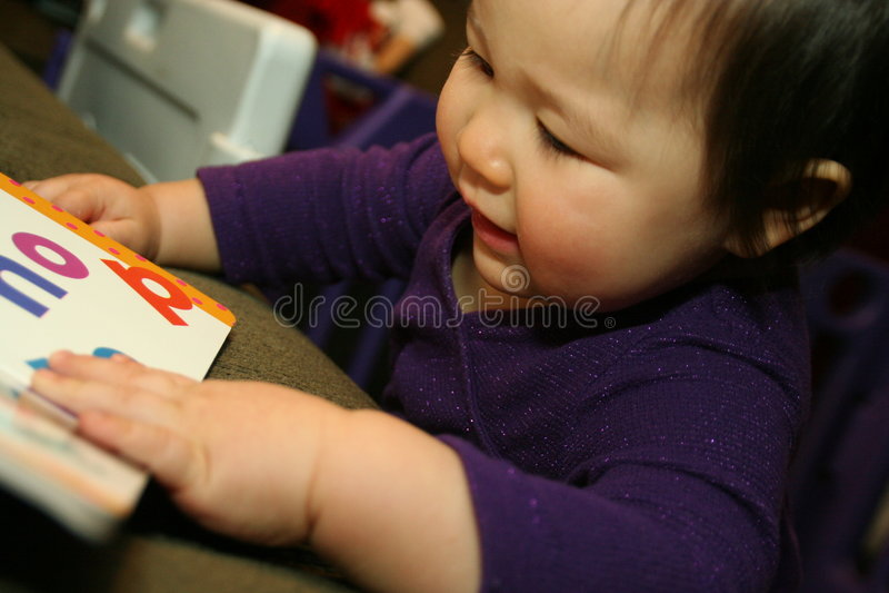 книга младенца во первых она читает стоковые изображения