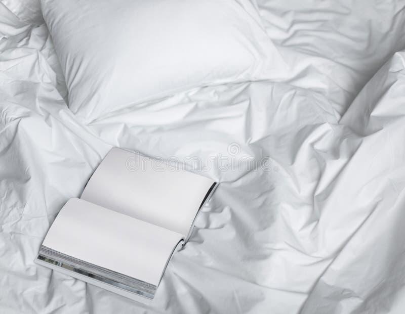 Книга на грязной кровати, творческий состав фото с книгой и белая кровать под светом солнца из окна стоковые изображения