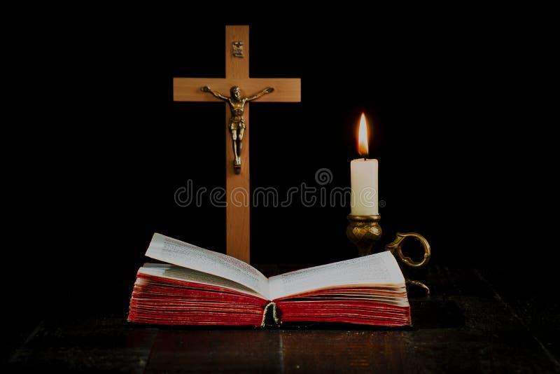 Книга на предпосылке распятия, и освещенная свеча в cand стоковые изображения rf