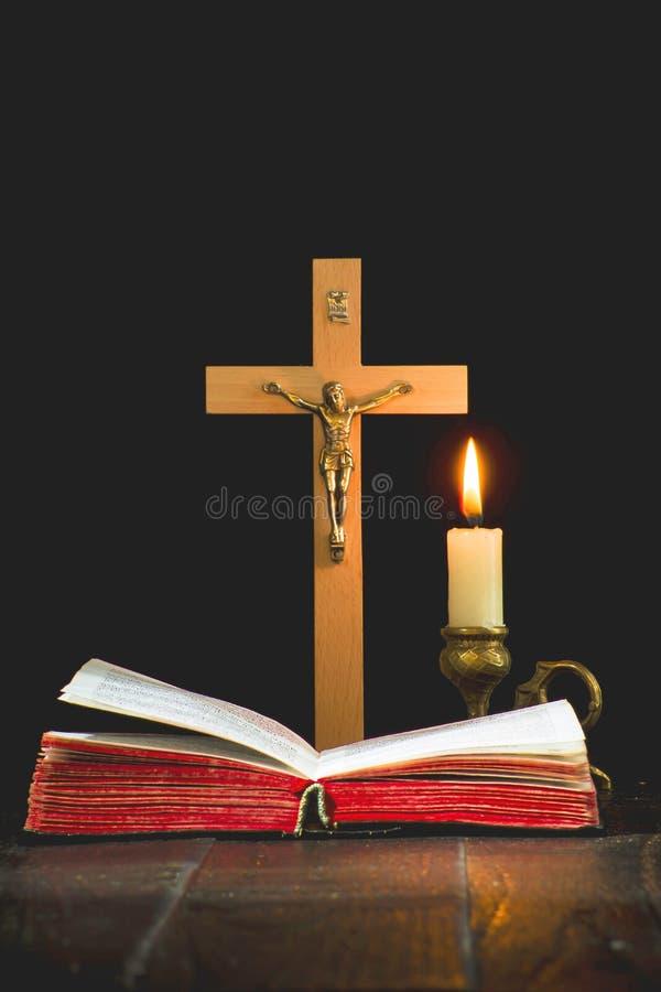 Книга на предпосылке распятия, и освещенная свеча в cand стоковое изображение rf