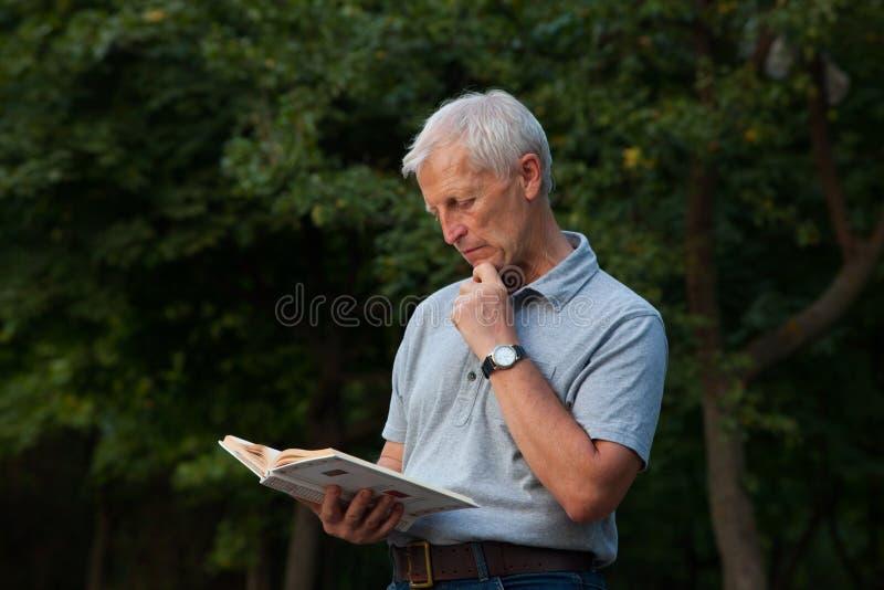 Книга положения и чтения старика стоковая фотография rf
