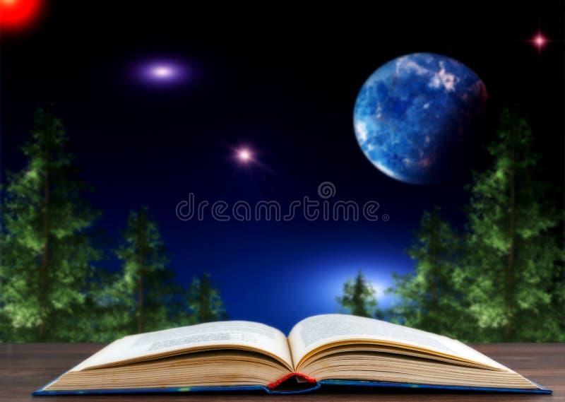 Книга против фона ландшафта с хвойными деревьями и ночным небом со звездами стоковые фотографии rf