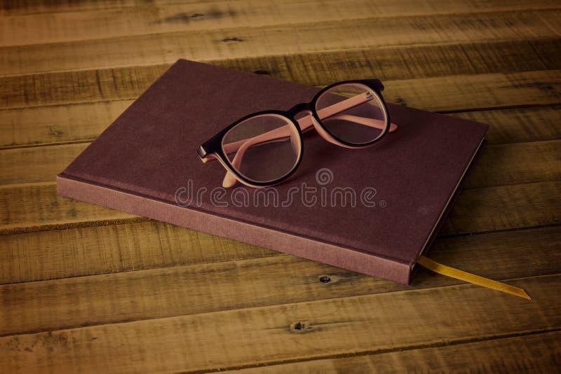 Книга с стеклами на деревянной предпосылке стоковые фотографии rf