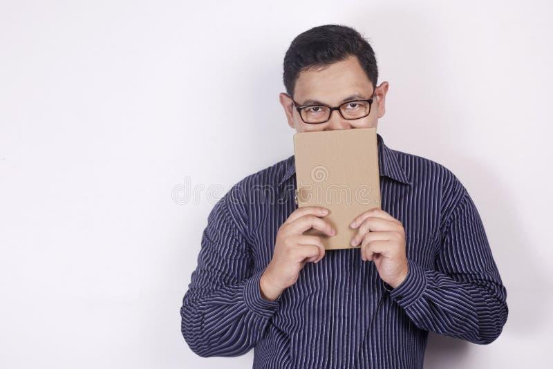 Книга удерживания молодого человека, рот покрытый книгой стоковые фотографии rf