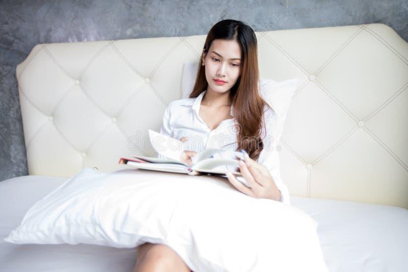 Книга чтения азиатских женщин любимая на белой спальне сняла на Amaz стоковые изображения
