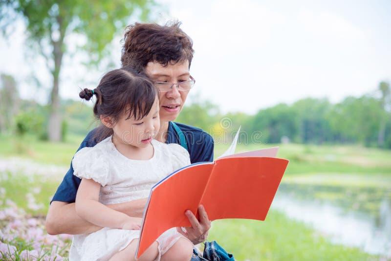 Книга чтения бабушки для ее внучки стоковое фото rf