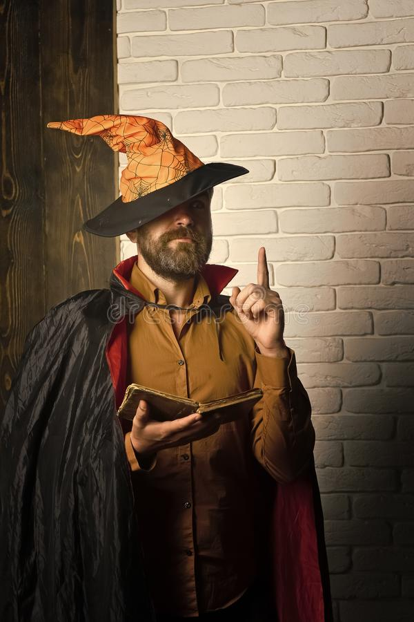 Книга чтения волшебника хеллоуина на кирпичной стене стоковое изображение