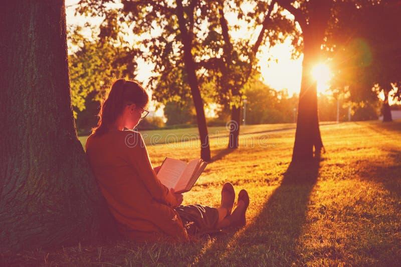 Книга чтения девушки на парке стоковая фотография rf