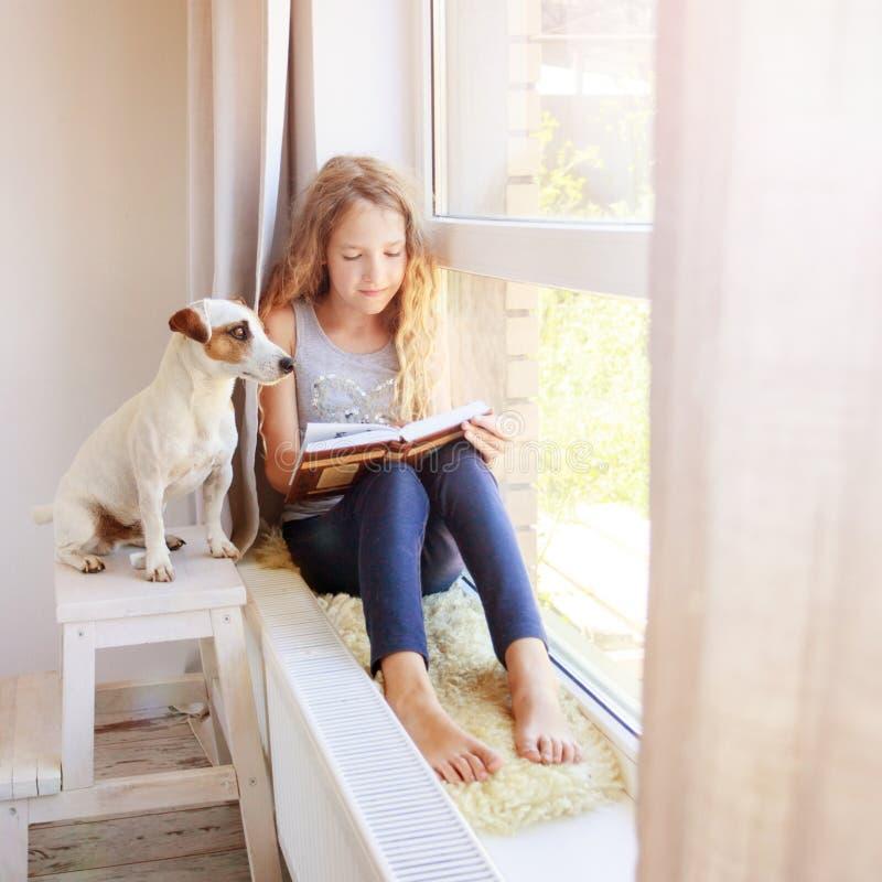 Книга чтения девушки дома стоковое изображение