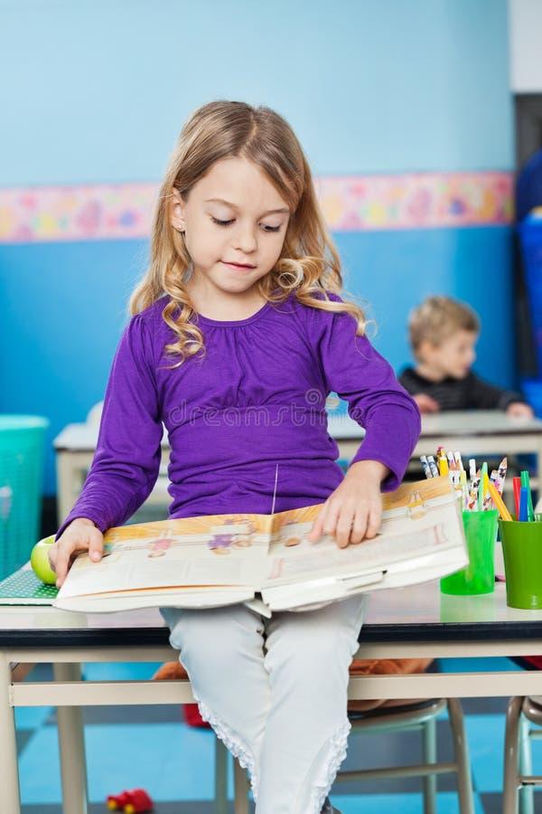 Книга чтения девушки пока сидящ на столе на стоковые фото