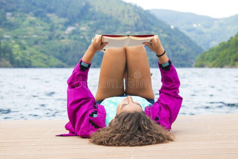 Книга чтения женщины на доке стоковое изображение