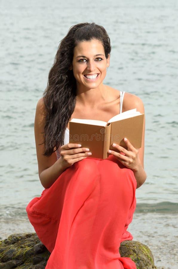 Книга чтения женщины счастливая около моря стоковые изображения