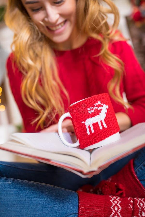Книга чтения женщины с горячим питьем стоковая фотография