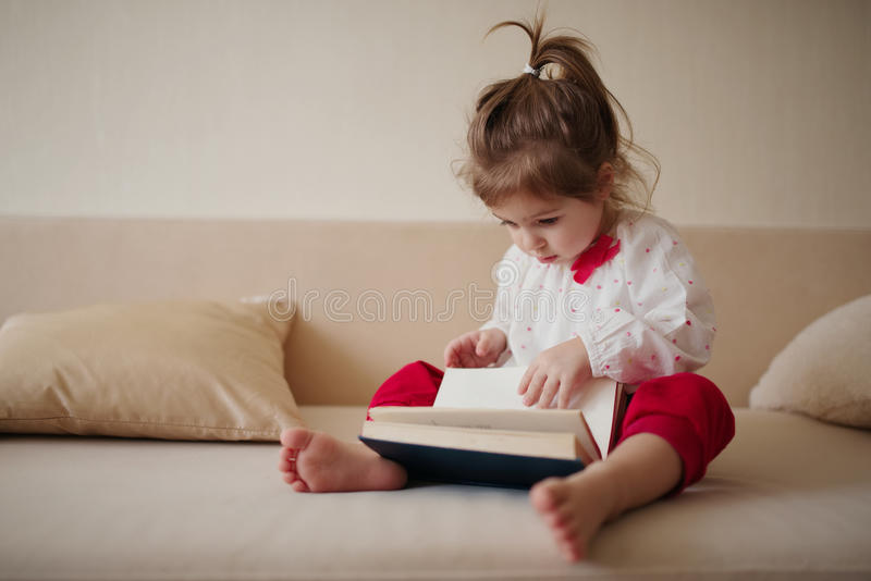 Книга чтения маленькой девочки дома стоковые изображения