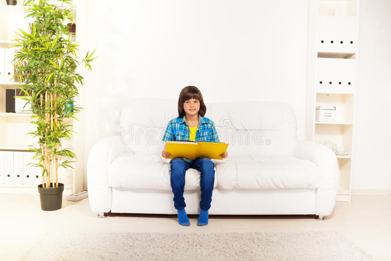 Книга чтения мальчика дома стоковые изображения