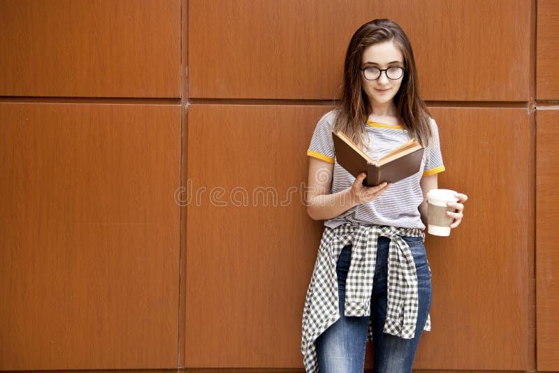 Книга чтения молодого студента женская в outdoors стоковое фото rf