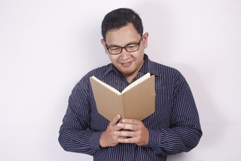 Книга чтения молодого человека, усмехаясь выражение стоковые изображения rf