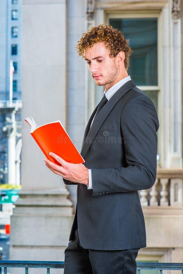 Книга чтения молодого человека снаружи стоковые изображения rf