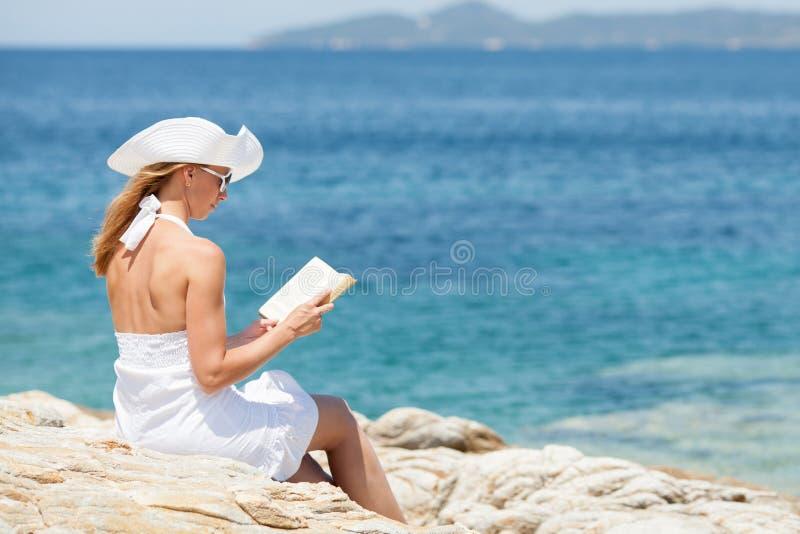 Книга чтения молодой женщины на пляже стоковое изображение rf