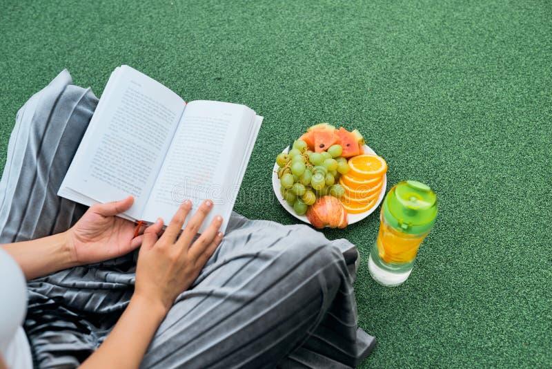 Книга чтения на лужайке, взгляд сверху женщины над плечом стоковые фотографии rf