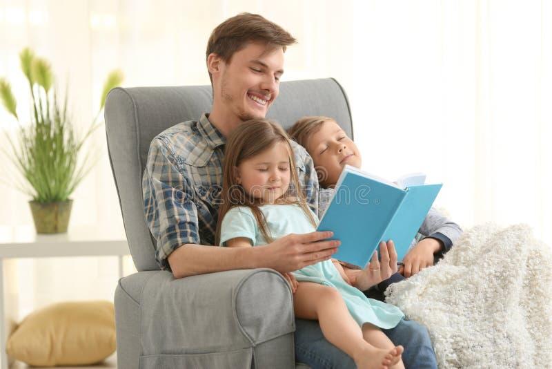 Книга чтения отца к его сонным детям дома стоковое изображение rf