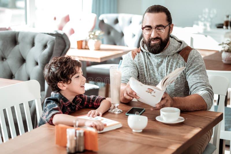Книга чтения папы для его заказа сына ждать в кафе стоковая фотография