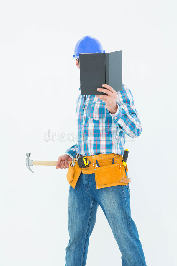Книга чтения плотника пока держащ молоток стоковое фото