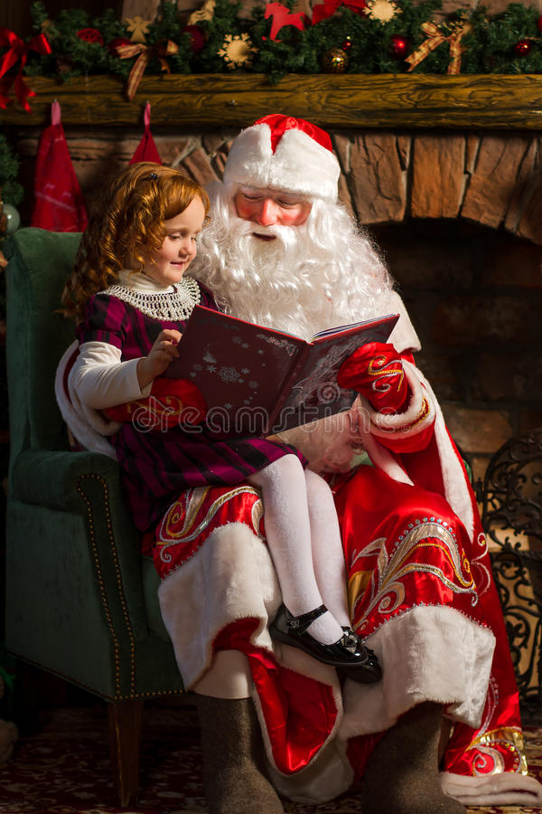 Книга чтения Санта Клауса и маленькой девочки стоковая фотография rf