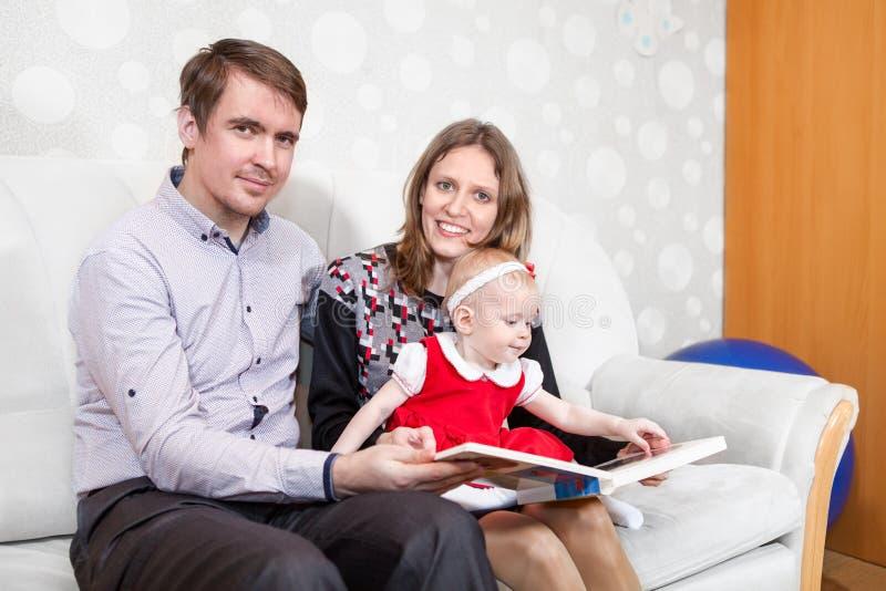 Книга чтения семьи 3 людей в отечественной комнате стоковые фото