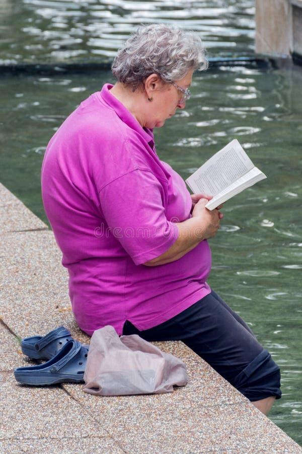 Книга чтения старухи с ногами в здоровой воде стоковое изображение rf