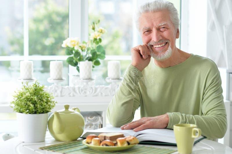Книга чтения старшего человека пока выпивающ чай стоковое фото rf