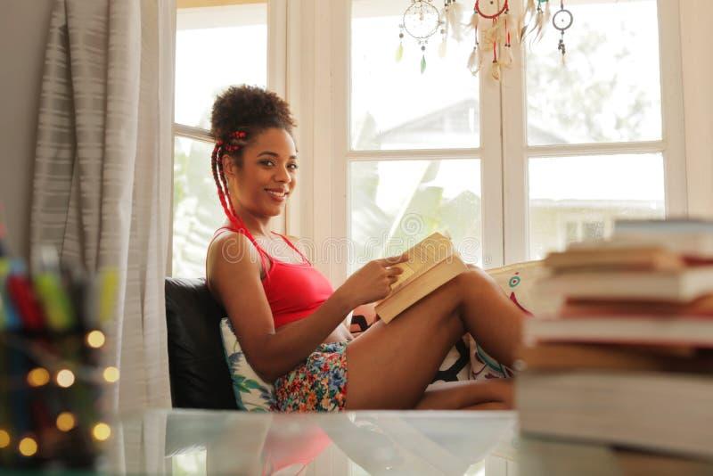 Книга чтения чернокожей женщины портрета и усмехаться на камере стоковые фото