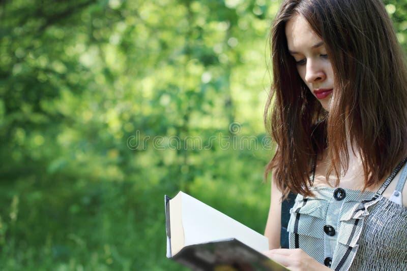 Книга чтения bbeautiful девушки крупного плана идя стоковые фотографии rf