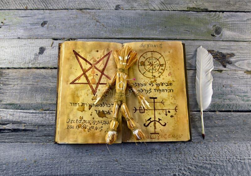 Книга Necronomicon с куклой voodoo стоковая фотография