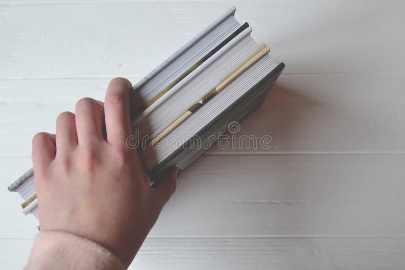 Книги в руке женщины на белой предпосылке стоковые изображения
