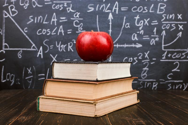 Книги и яблоко на деревянном столе, на фоне доски с формулами Teacher& x27; концепция дня s и назад к стоковое изображение rf