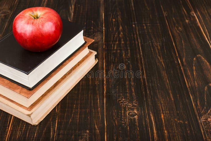 Книги и яблоко на деревянном столе r стоковые изображения