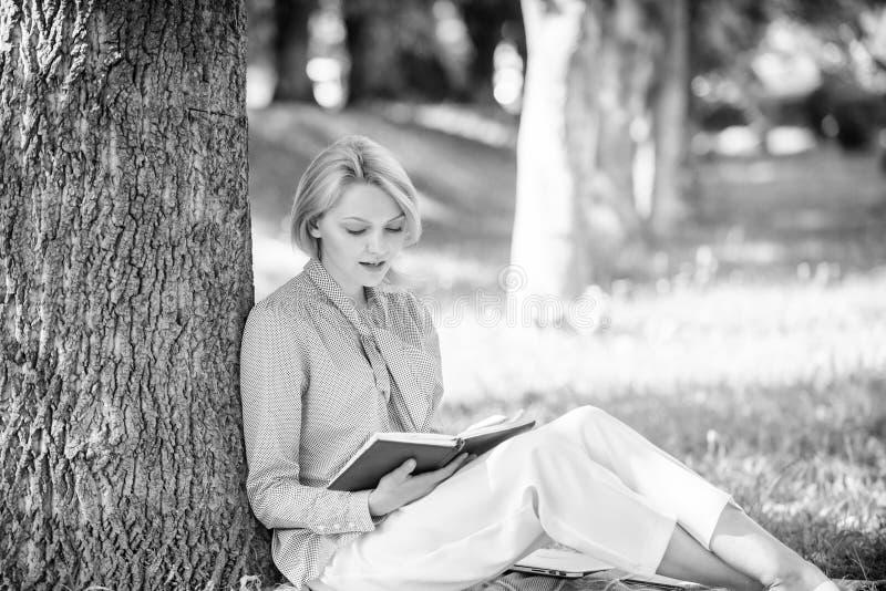 Книги каждая девушка должна прочитать Сконцентрированная девушка сидит парк постный ствол дерева прочитал книгу Чтение воодушевля стоковые фото