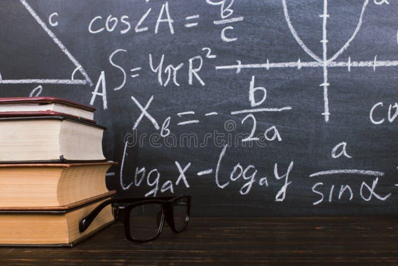 Книги на деревянном столе, на фоне доски мела с формулами Teacher' концепция и задняя часть дня s в школу стоковые изображения