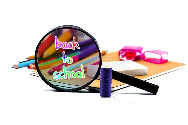 Книги, ручка, карандаш и лупа на белой доске, образовании и назад к вопросу школы, пути клиппирования стоковое фото
