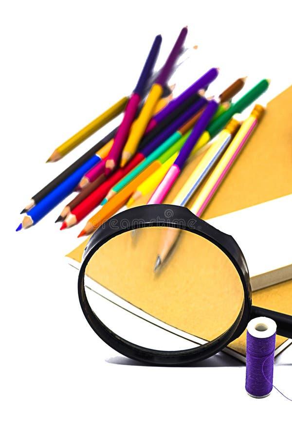Книги, ручка, карандаш и лупа на белой доске, образовании и назад к вопросу школы, пути клиппирования стоковые изображения